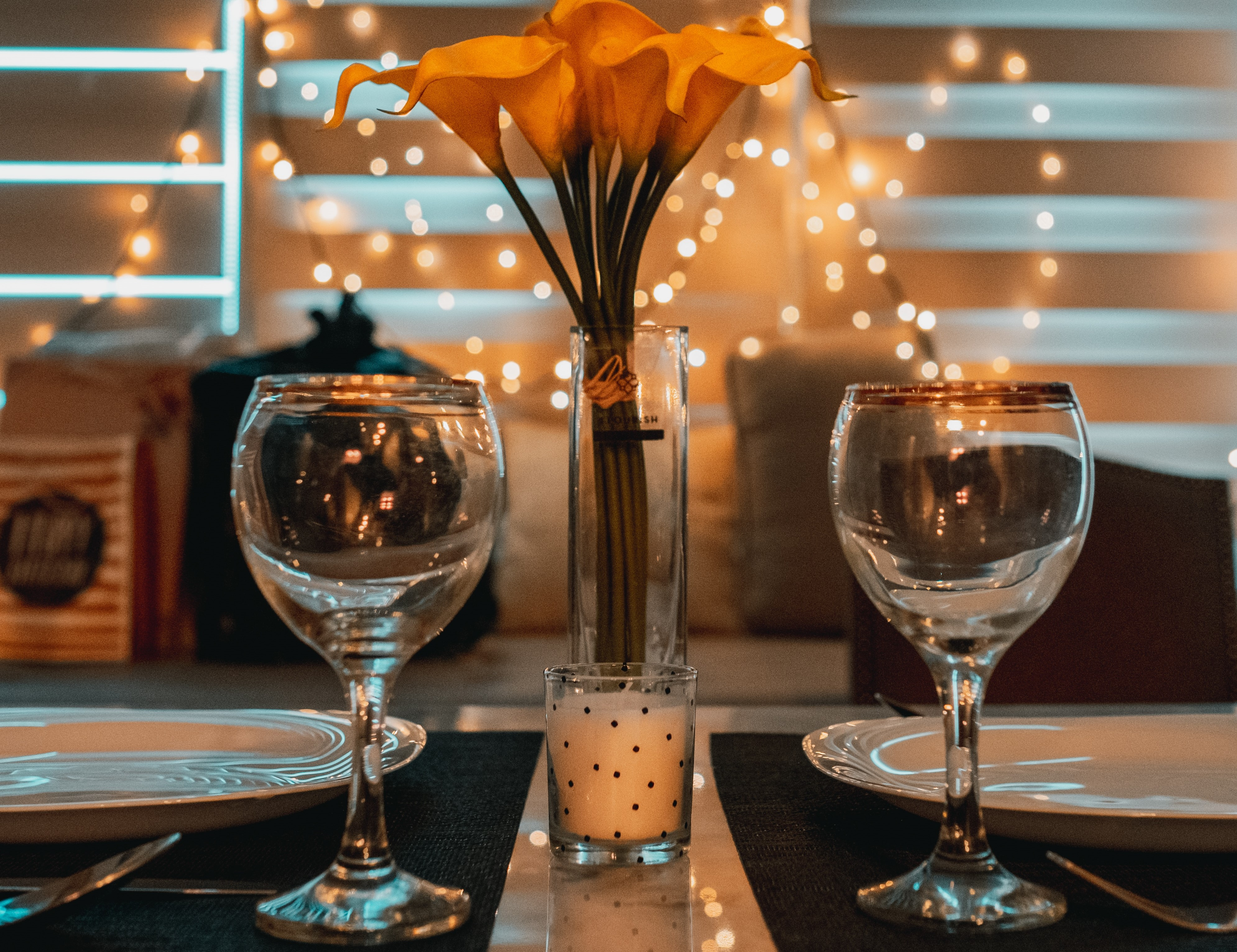 Two clear wine glasses on a table near an unlit tealight, by white plates, with a flower centerpiece, and lights all around.